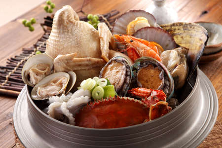 Big hot pot of Tang Emperor of the Sea with fresh octopus, abalone, crab, clams, shrimp and chicken on wooden korean table