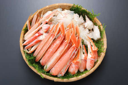 Raw fresh cold snow crab pot set with claws, legs, meat and herbs on bamboo tray Stock Photo