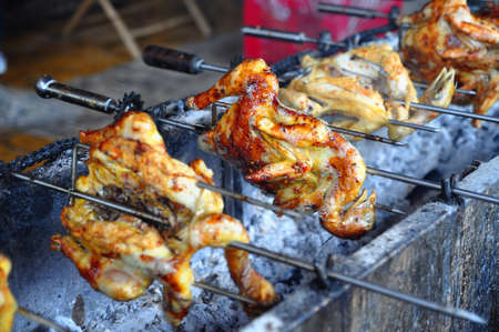 spit: Grilling whole chicken on hot charcoal in asia