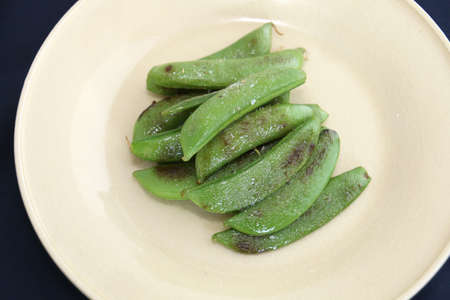 Fried green peas  on white platter