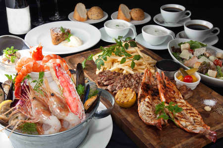 Table meal of seafood hot pot , beef, bbq, bread, shrimp, lobster and wine