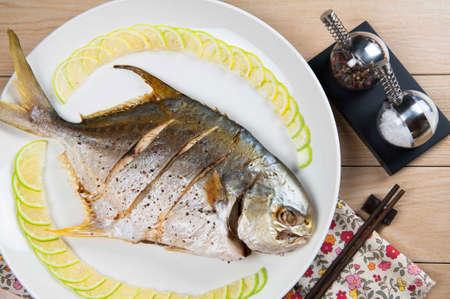 Grilled pompano fish on white dish Zdjęcie Seryjne
