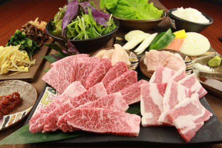 Fresh sliced beef with vegetables on tables in the kitchen