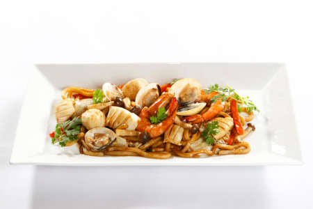 Sauteed seafood stuff with squid, clams, shrimp, mushoom and fish balls on white platter Stock Photo