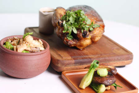 Fried whole chicken with quinoa and cabbage on wooden board