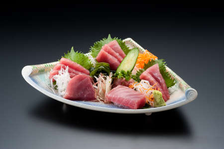 Dish of sashimi sushi tuna with cucumber, onion and wasabi