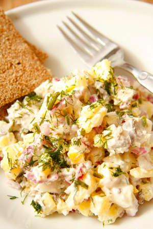 Herring and potato salad with capers on white dish 版權商用圖片