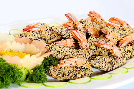 Fried shrimp with seasame and sliced cucumber on white dish