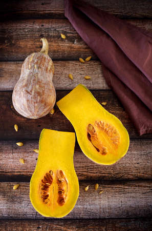 Fresh red pumpkin on wooden table with tablecloth Stock Photo