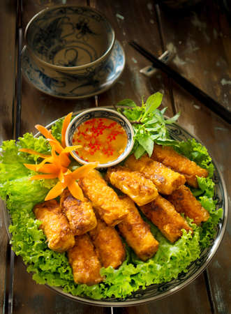 Vietnamese crispy spring rolls or Nem nuong with fish sauce and lettuce Stock Photo