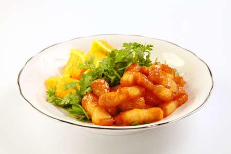 Sliced pork braised with oranges on white dish