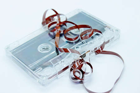 Old audio cassette tape located on a white background
