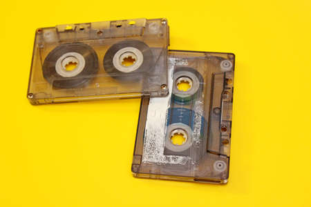 Old audio cassettes laid out on a yellow background Фото со стока