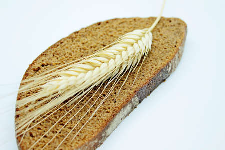 A piece of bread and rye spike located on a white background Stok Fotoğraf