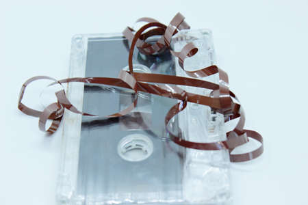 Plastic transparent audio cassette located on a white background