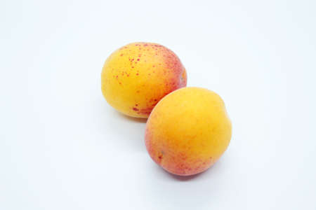 Tasty ripe beautiful apricots located on a white background