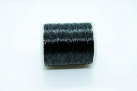 The black thread coil is located on a white background