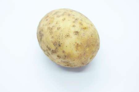 Raw ripe potatoes are located on a white background