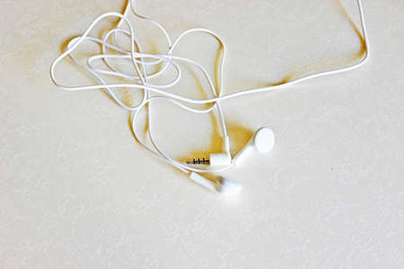White little headphones located on a white background