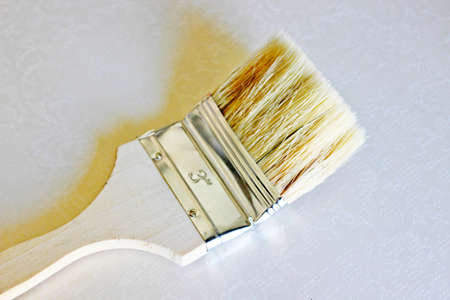 The paintbrush with a wooden handle is located on a white background