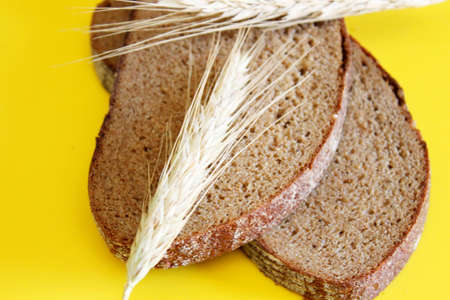 Pieces of sliced rye bread and ripe ears of rye are located on a yellow background