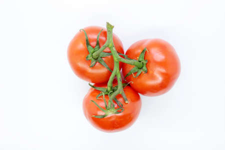 Beautiful ripe red tomatoes are located on a white background