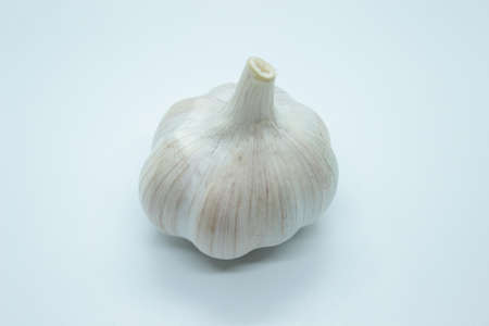 The root of ripe garlic is located on a white background
