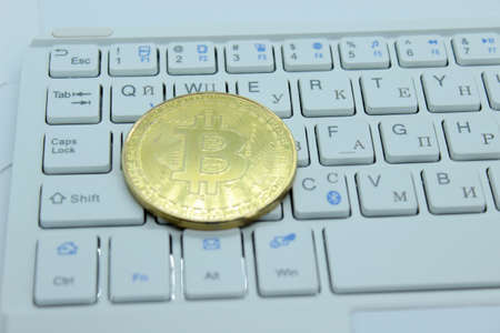 Gold Bitcoin located on a white keyboard, cryptocurrency
