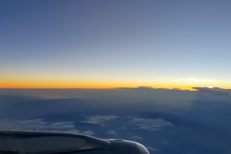 Sunset up above the clouds viewed inflight on a passenger airplane Stok Fotoğraf
