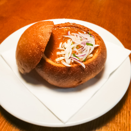 Dish of czech cuisune bread bowl and beef goulash soup with onion slices