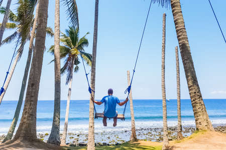 Tourist swings on a swing on the beach overlooking the Indian Ocean near Charlie Chocolate Factory in Bali, Indonesia Stok Fotoğraf