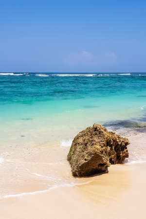 Day view on stone and Indian ocean and on Karma beach with white sand on Bali, Indonesia