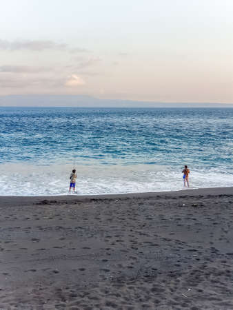 BALI, INDONESIA - SEPTEMBER 18: Men fish on a black sand beach at the evening at September 18, 2018 in Bali, Indonesia