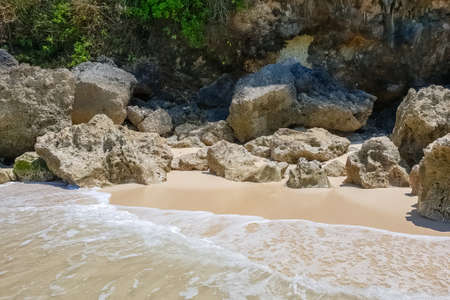 Day view on stones and rocks and white sand on Karma beach on Bali, Indonesia Stok Fotoğraf