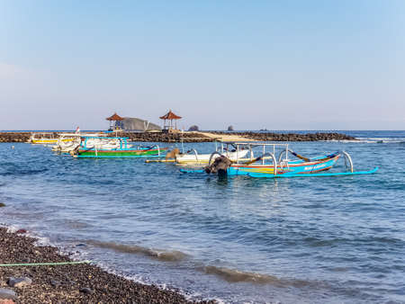 Scenic view of boat, Indian ocean and blue clear sky on Candidasa beach in Bali, Indonesia