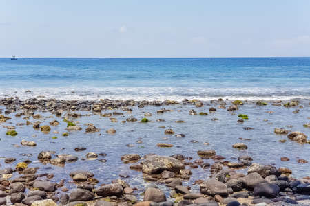 View on Indian ocean coast with pebble and sand beach near Charlies Chocolate factory on Bali, Indonesia