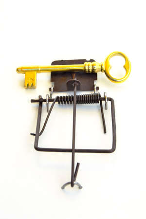 GOLD KEY ON A MOUSETRAP - Mousetrap with a gold house key as a bait.