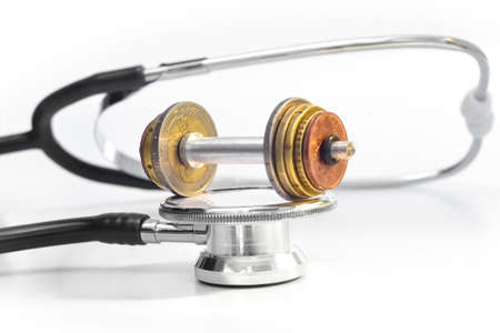 MEDICAL EXPENSES 3 - A stethoscope with a euro-coin-weight-lift on top.