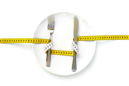 ON A DIET - A fork and a knife wrapped with a measure and placed on an empty dish. Zdjęcie Seryjne