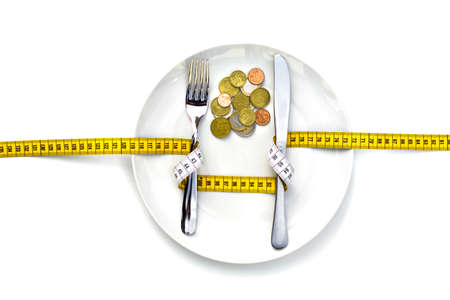 MONEY CANNOT BE EATEN - A fork & knife wrapped with a measure, and placed on a dish that has money inside instead of food.