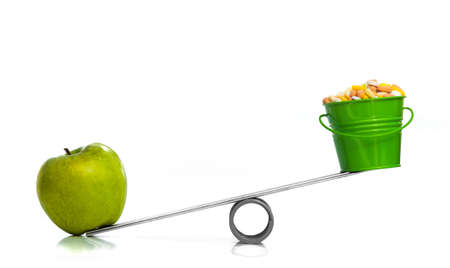ONE APPLE VS A BUCKET OF PILLS - One green apple and a bucket of pills competing on a seesaw.