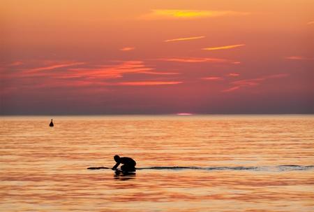 watersports: Surfer in the water at sundown against orange sky.
