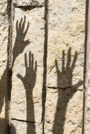 Shadow of humans hand on the stone wall photo