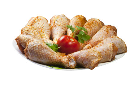 Chicken legs with tomato on plate and white background photo