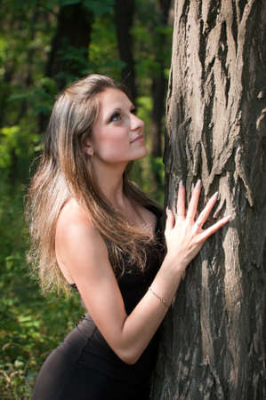 face in tree bark: Photo of young beautiful girl embracing tree trunk