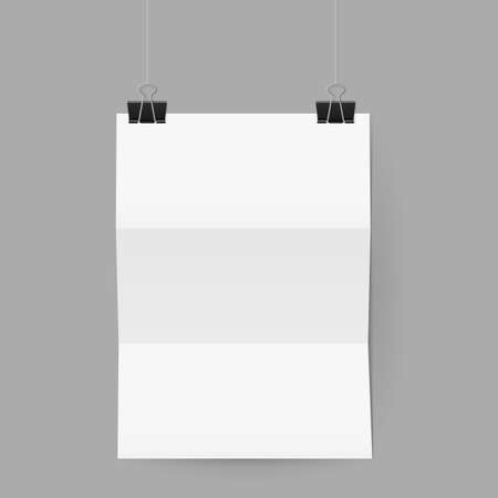 folded paper: White sheet of paper folded in three. The paper hangs on black binder clips.