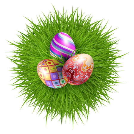 Three brightly colored Easter eggs on a round patch of green grass over white background to celebrate the festive season.