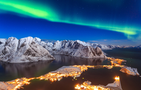 Unique chance to watch the beautiful dancing Aurora Borealis over the winter Reinebringen mountain ridge and Reinefjord, Lofoten, Norway