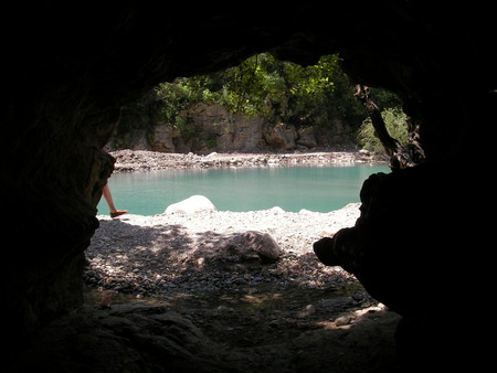 formed: Big cave with a beautiful view of the lake formed by the mountain river in a canyon Geynyuk