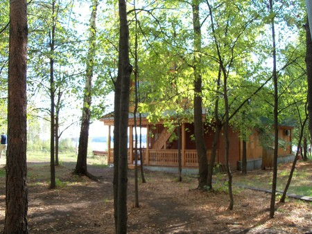 was: In a grove among trees the small lodge for an outdoor recreation was sheltered